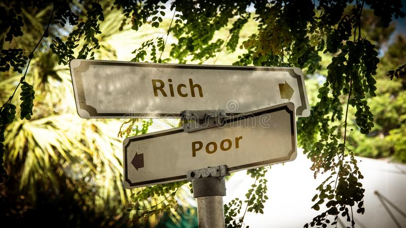 Street sign rich versus poor. Street sign the direction way to rich versus poor royalty free stock images