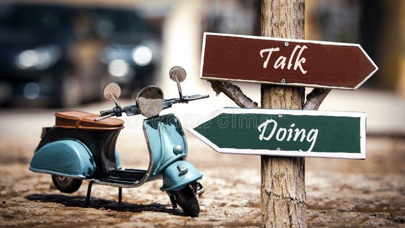 Street Sign to Doing versus Talk. Street Sign the Direction Way to Doing versus Talk stock photo