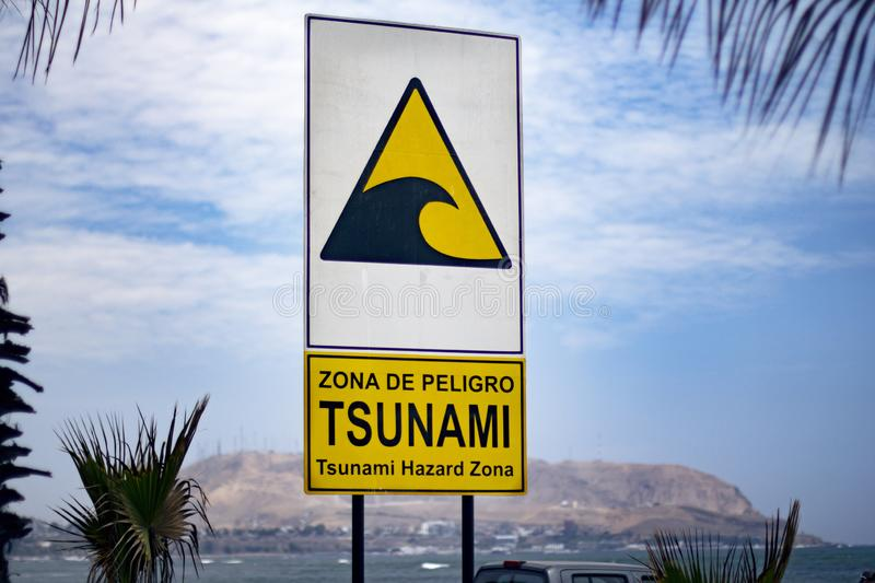 Street sign of `tsunami hazard zone` meeting point beside the ocean royalty free stock images