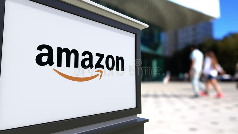 Street signage board with Amazon.com logo. Blurred office center and walking people background. Editorial 3D rendering stock illustration