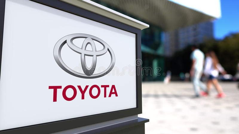 Street signage board with Toyota logo. Blurred office center and walking people background. Editorial 3D rendering royalty free illustration