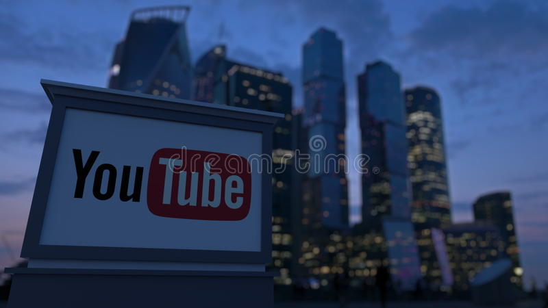 Street signage board with YouTube logo in the evening. Blurred business district skyscrapers background. Editorial 3. D stock photo