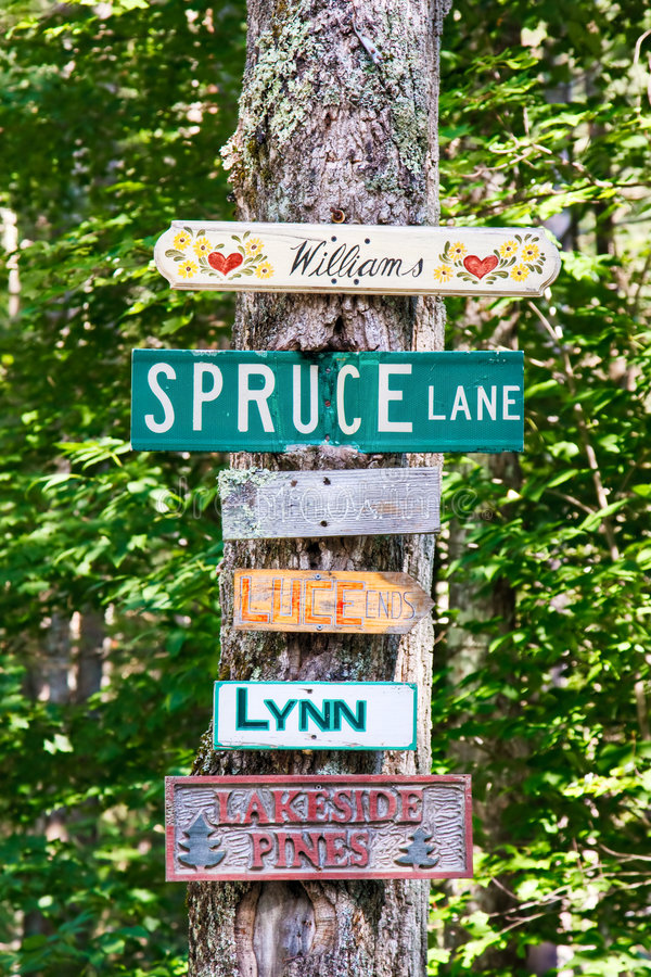 Street Signs. And family home signs nailed to a tree on a country road stock images