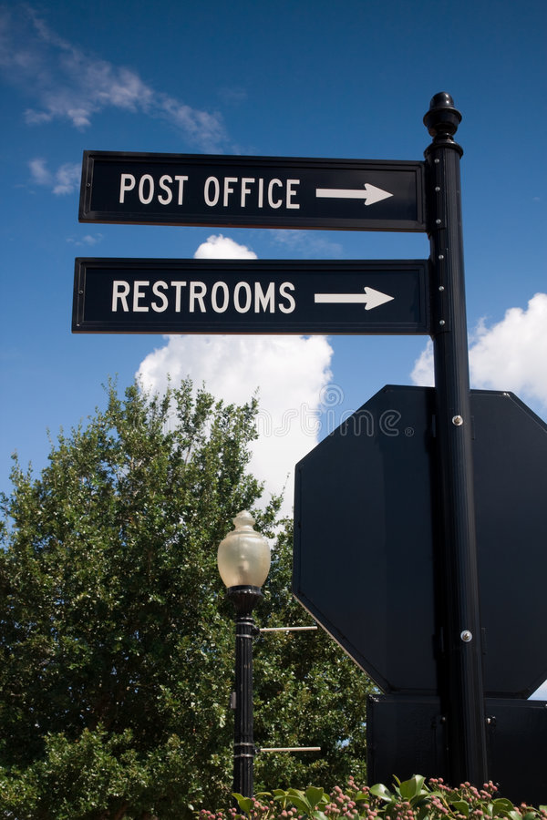 Street Signs. Pointing the way to the post office and restrooms royalty free stock image