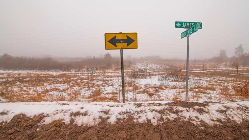 Street signs and arrows sign - cross-section of two rural gravel roads in Northern Wisconsin - cold snowy winter day in the gras. Sland / prairie / frozen royalty free stock image