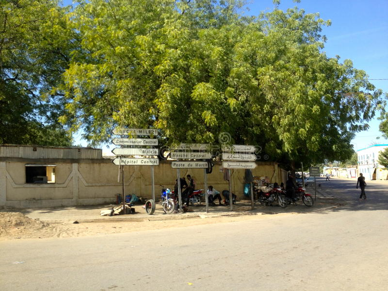 Street signs in the centre of N'Djamena, Chad. Street signs of which a lot still in French. The former colonial power of Chad. Local people relaxing in the shade stock photography