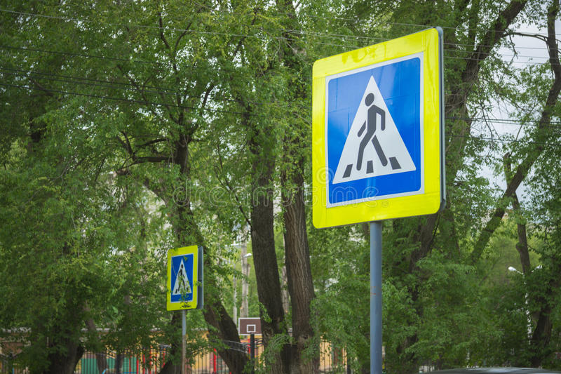 Street signs. A crosswalk street signs with trees on background stock images