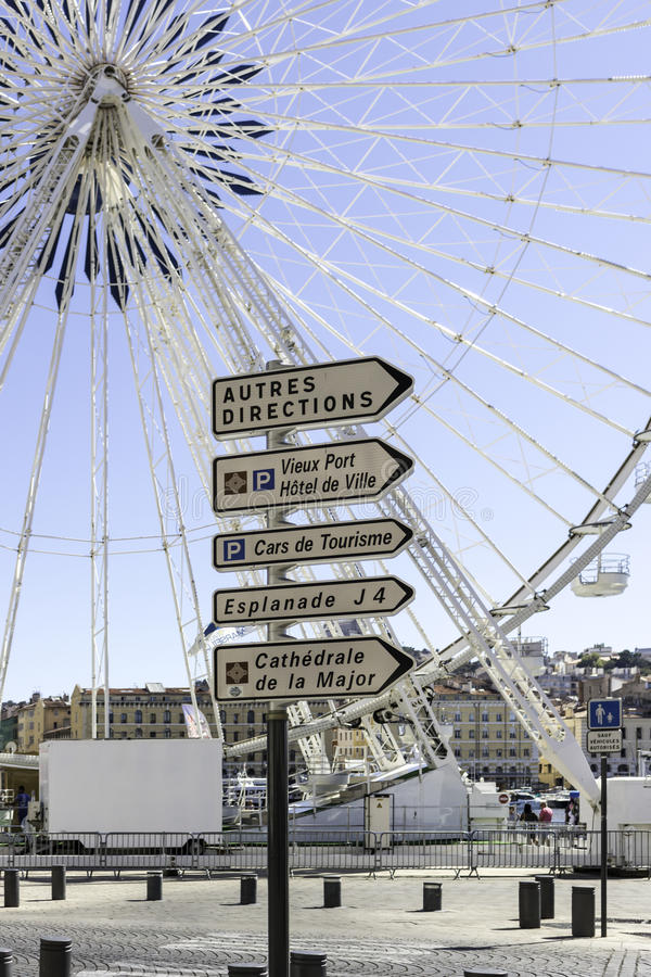 Street signs and Ferris Wheel in the Old Port area of Marseille, France. stock photo