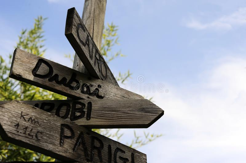 Street signs in the natural park indicating directions to different places of the world. The sky on the background. Taken in north Italy stock images