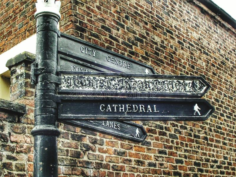 Street signs. Street sign on a black pole with cathedral and city centre on next to a brick wall royalty free stock image