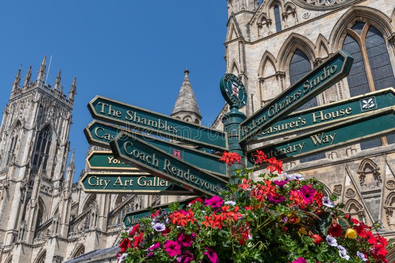 Street signs in York, England, UK. Street signs in the city of York. York Minster is in the background and there is a beautiful floral display in the foreground stock photos