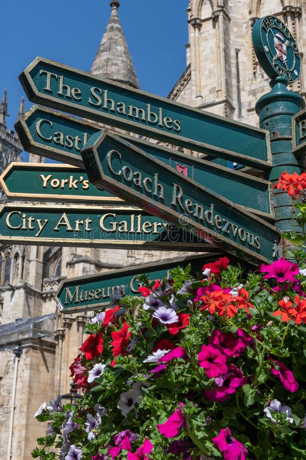 Street signs in York, England, UK. Street signs in the city of York. York Minster is in the background and there is a beautiful floral display in the foreground royalty free stock photography