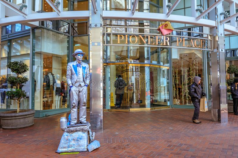 Street silver painted artist in front of Pioneer Place mall in d. Portland, United States - Dec 20, 2017 : Street silver painted artist in front of Pioneer Place stock image