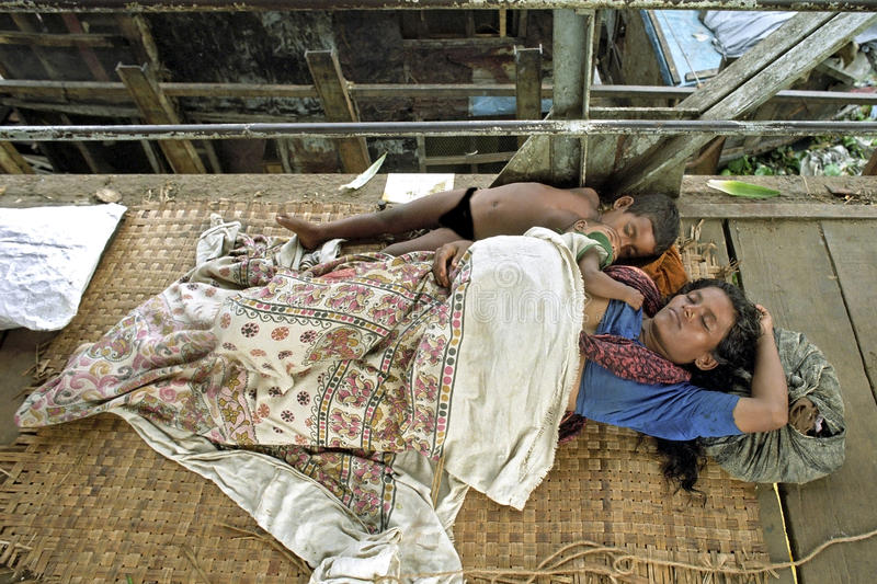 On street sleeping homeless mother with children. Bangladesh, capital, city Dhaka: In the harbor for passenger boats Sadarghat sleeping woman with small children stock image