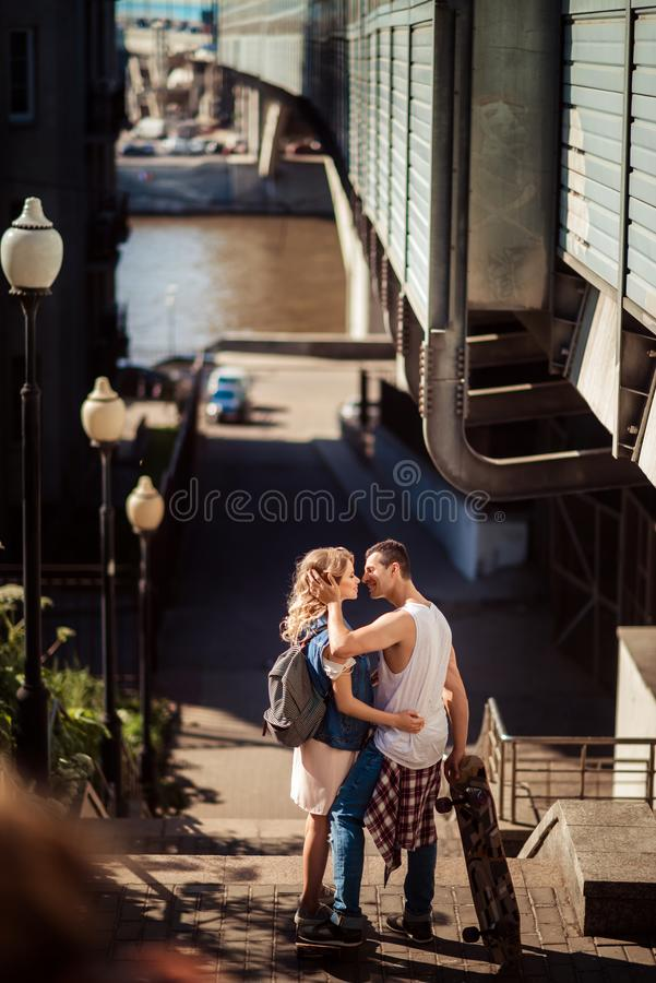 Street sport and hobby concept. Vertical shot of lovely couple of skaters have break after skating, embrace and going to stock photo