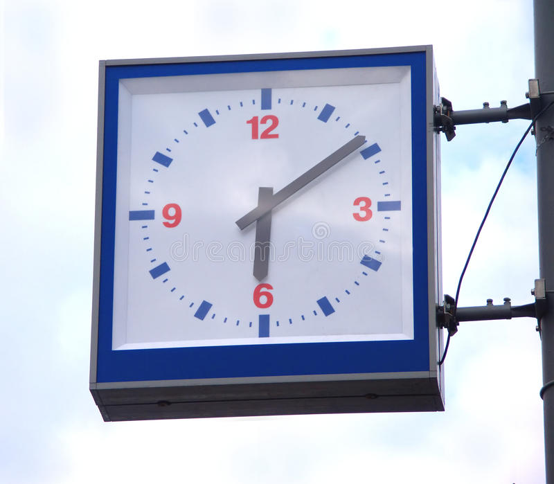 Street square clocks on blue sky with clouds. Street square clocks with red digits on blue sky with clouds stock photos