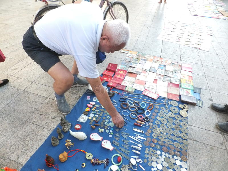 The street stall, selling old books and ancient coins. People are watching, and buying. In Shenzhen, china stock image