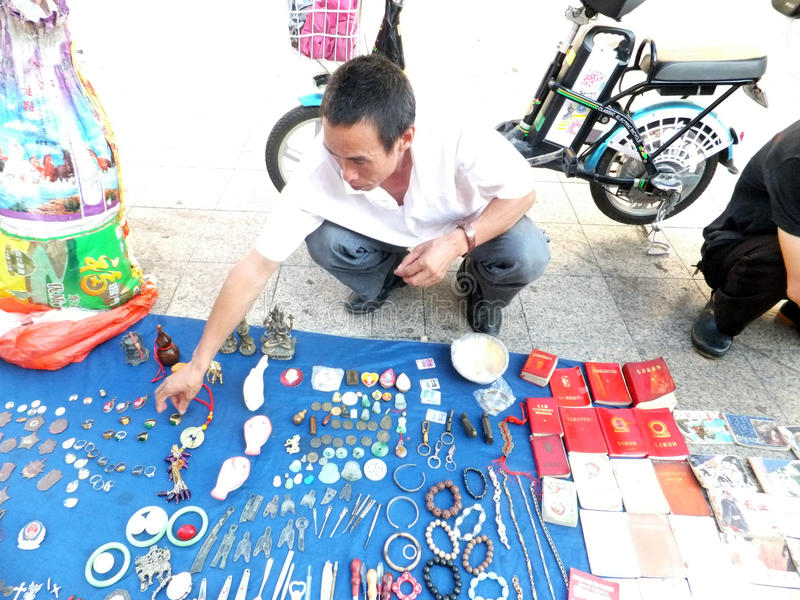 The street stall, selling old books and ancient coins. People are watching, and buying. In Shenzhen, china stock photography