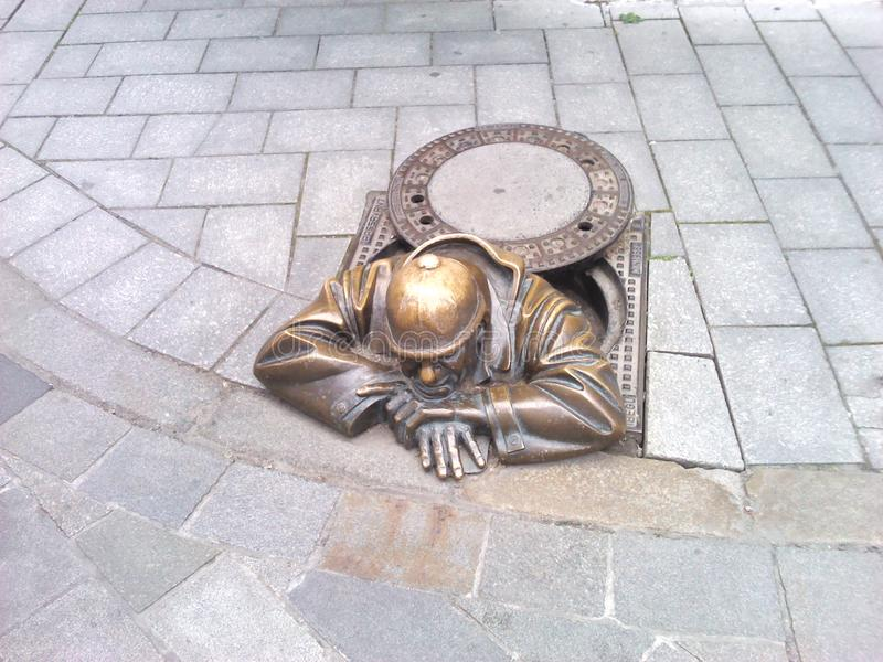 Street statue in Bratislava. Tired plumber man. royalty free stock images