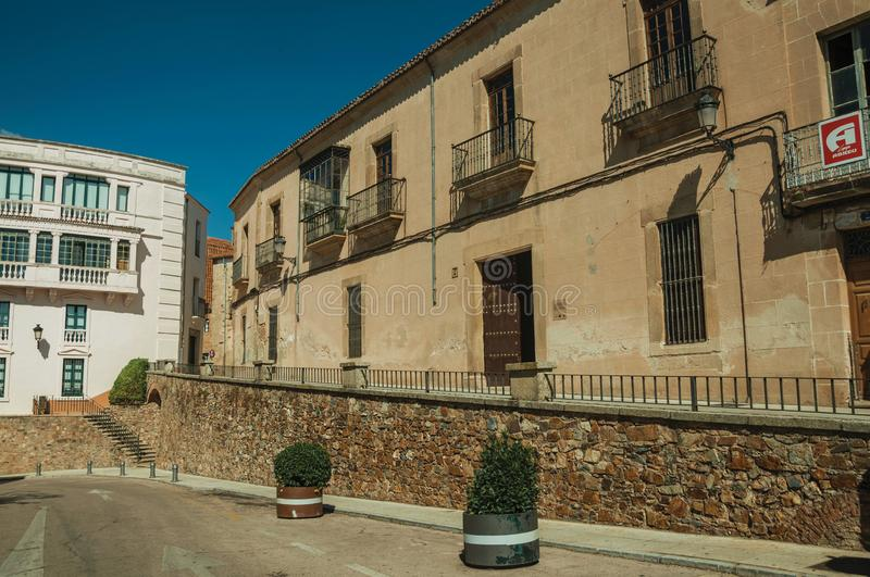 Street with stone wall and old buildings at Caceres royalty free stock photos