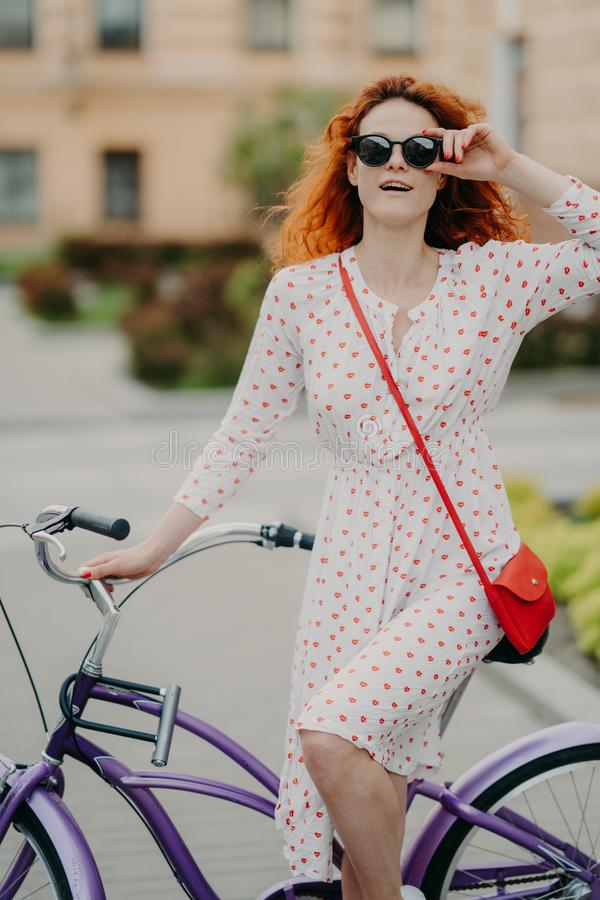 Street style and active rest concept. Curly red haired woman keeps hand on frame of sunglasses, wears white dress, focused into stock photography