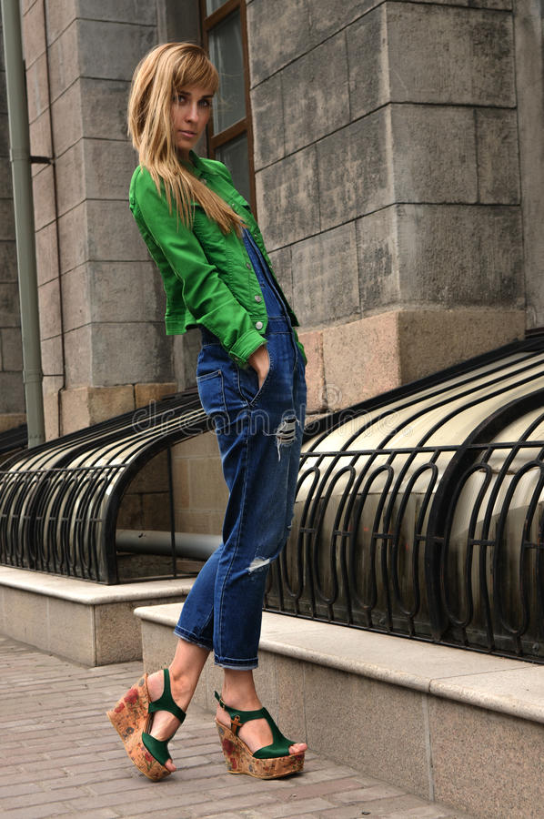 Street style fashion girl. Full length portrait of a fashion model posing over city background royalty free stock images