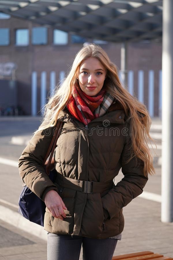 Street style fashion portrait of young woman waiting at bus station. On a sunny day in winter stock image