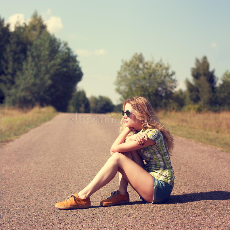 Street Style Fashion Woman Sitting on the Road Outdoors. Toned Instagram Styled Photo with Copy Space. Modern Youth Lifestyle Concept royalty free stock photos