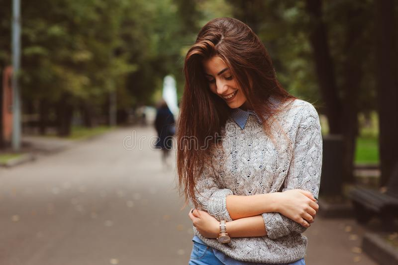 Street style portrait of young beautiful happy girl walking in autumn city royalty free stock photography