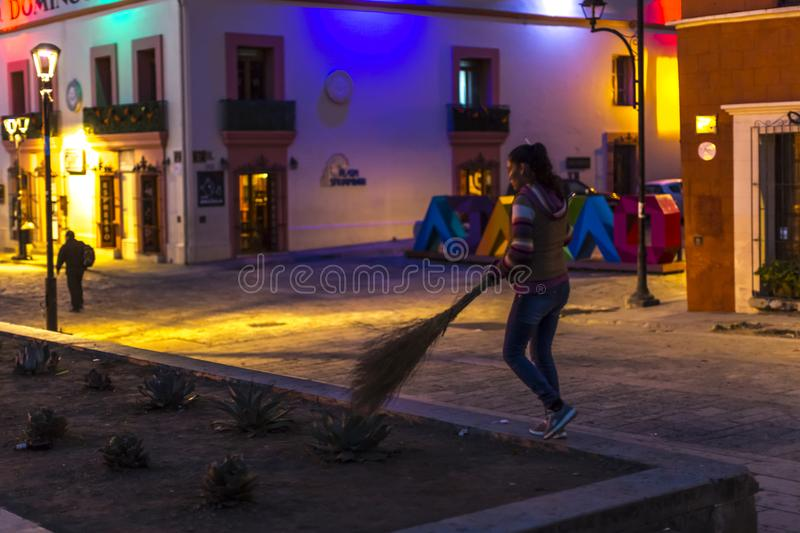 Street Sweeper. A young woman sweeps the streets of Oaxaca, Mexico after Day of the Dead celebrations stock photography