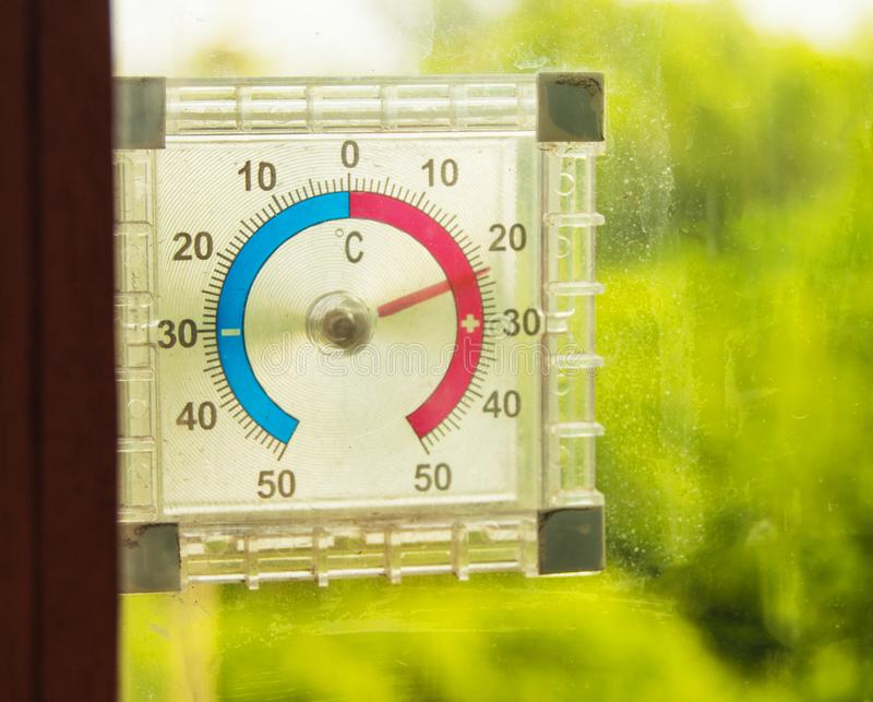 Street thermometer hanging on the window and shows the temperature of the air in the summer against the green trees royalty free stock images