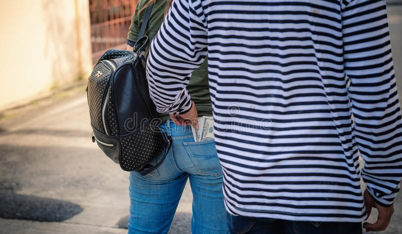 Street thief stealing money from back pocket of jeans woman., Robber, Thief concept royalty free stock photos
