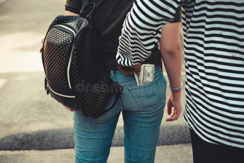 Street thief stealing money from back pocket of woman`s jeans, R royalty free stock photography
