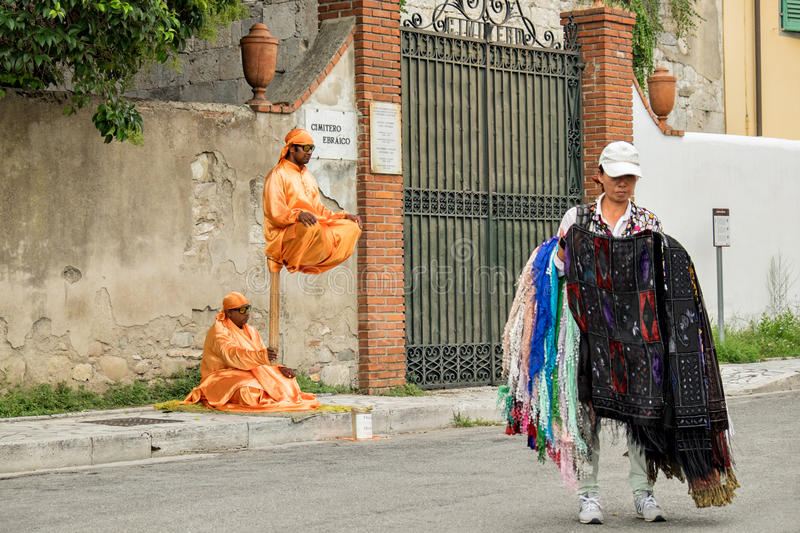 Street Trader and Performers Pisa Italy including a Clothing Trader and Illusionist stock images