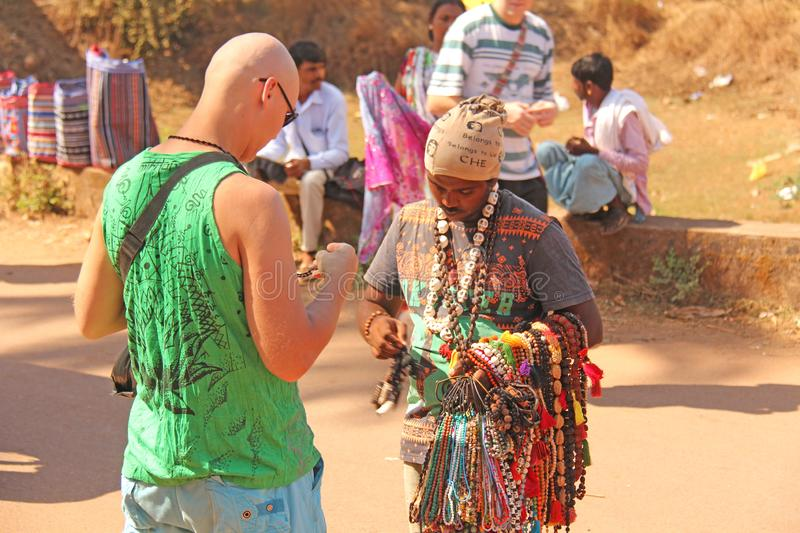 Street trading. Bald Tourist European buys beads or jewelry from an Indian seller. The seller on the street sells his goods. India, GOA, January 24, 2018 stock images