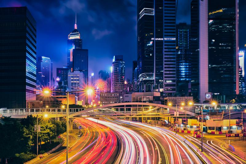 Street traffic in Hong Kong at night. Office skyscraper buildings and busy traffic on highway road with blurred cars light trails. Hong Kong, China royalty free stock photography