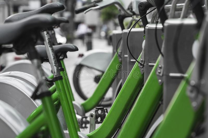Street transportation green hybrid rent bicycles with electronic form of payment for traveling around the city stand in. Row royalty free stock photos