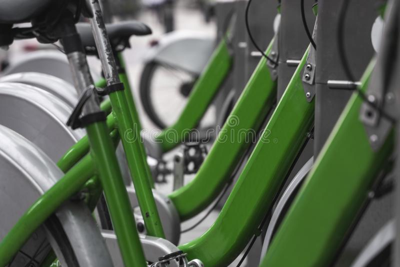 Street transportation green hybrid rent bicycles with electronic form of payment for traveling around the city stand in. Row stock photo
