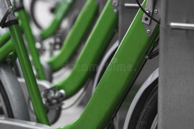Street transportation green hybrid rent bicycles with electronic form of payment for traveling around the city stand in. Row stock images