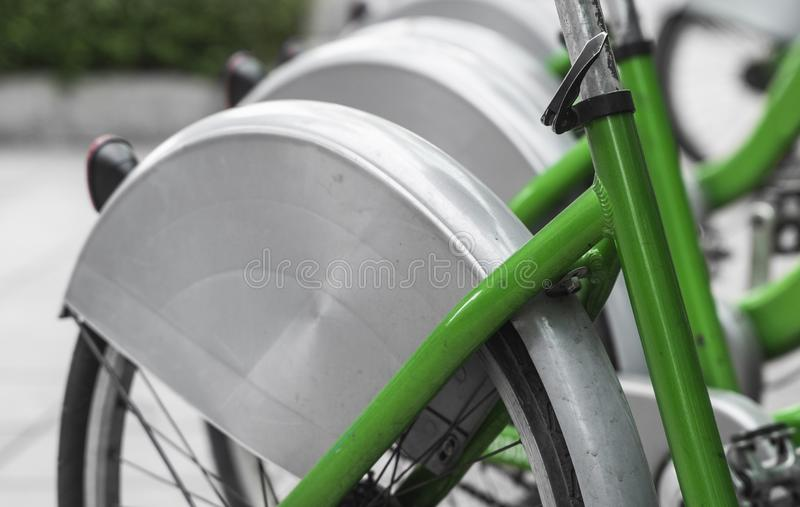 Street transportation green hybrid rent bicycles with electronic form of payment for traveling around the city stand in. Row royalty free stock photo