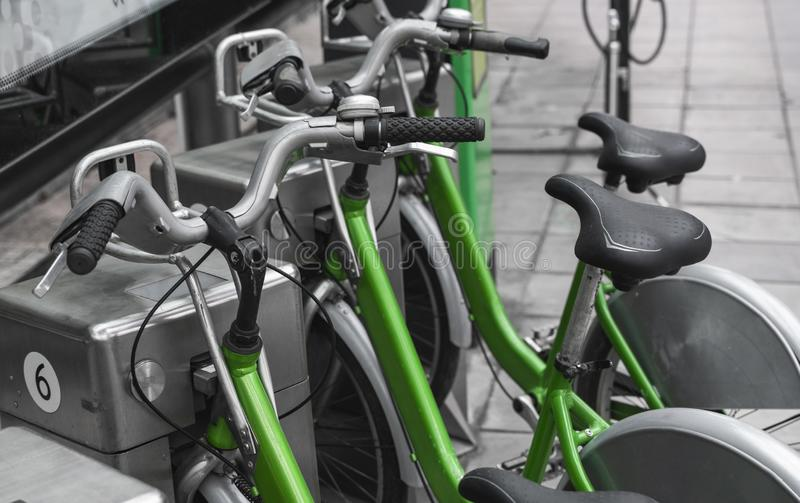 Street transportation green hybrid rent bicycles with electronic form of payment for traveling around the city stand in. Row stock image
