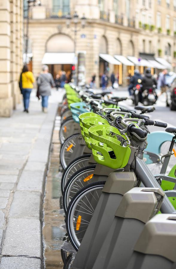 Popular bikes for public rental stand at parking station on street in Paris ready for use. Street transportation green public rent bicycles with basket for stock images