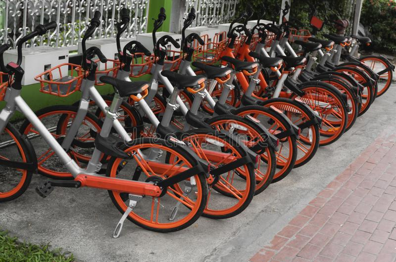 Street transportation orange hybrid rent bicycles with electronic form of payment for traveling around the city stand in. Row stock images