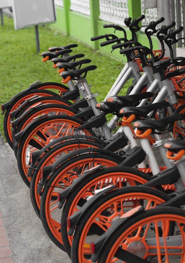 Street transportation orange hybrid rent bicycles with electronic form of payment for traveling around the city stand in. Row royalty free stock images
