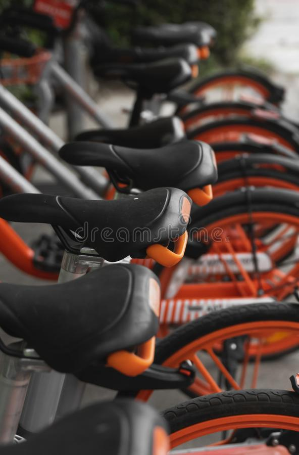 Street transportation orange hybrid rent bicycles with electronic form of payment for traveling around the city stand in. Row royalty free stock photo