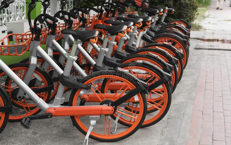 Street transportation orange hybrid rent bicycles with electronic form of payment for traveling around the city stand in. Row stock image