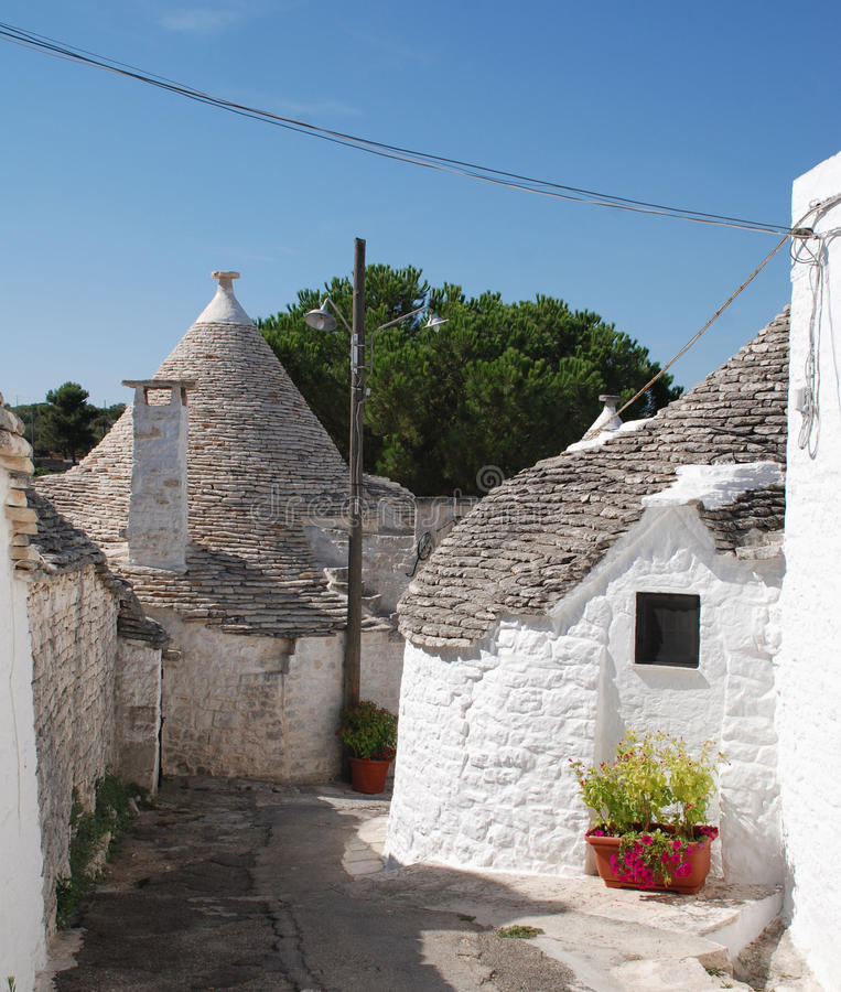 Street of Trulli. A street of trulli in Alberobello in Puglia, southern Italy. The trulli, which are protected under UNESCO World Heritage laws, are traditional stock photo