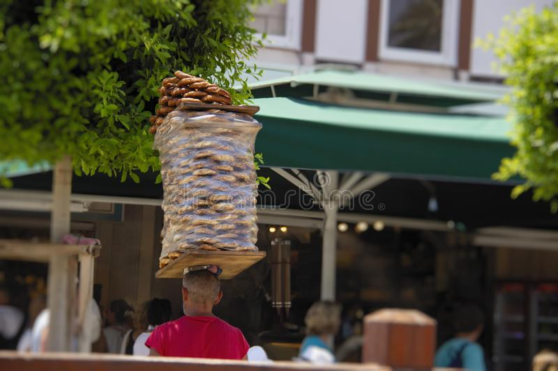 Street vendor carries stack of bagels simit on his head. Simit is traditional turkish berakfast snack, very popular in Turkey royalty free stock image