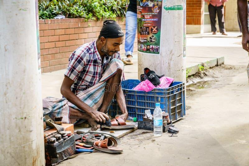 Street vendor in Chittagong, Bangladesh. Chittagong, Bangladesh, December 22, 2017: shoe repair service on a street of Chittagong in Bangladesh stock photography