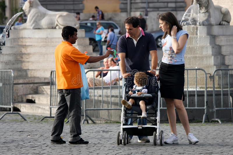 Street vendor and couple with child in stroller stock photography